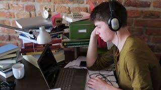Student surfing on internet and listening music on headphones
