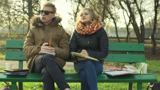 Students sitting on the bench in the park and girl looking worried