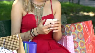 Stylish girl in red dress sitting in the bench and texting on smartphone
