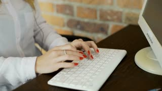 Stylish woman with red nails working on computer in the office