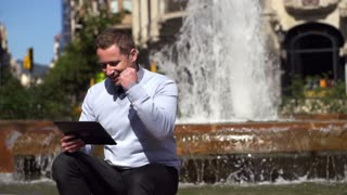 successful businessman looking at good results on tablet and sitting