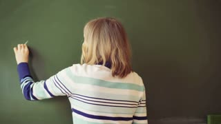 Teacher standing back and writing numbers on blackboard