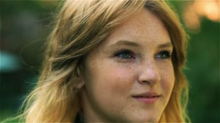 Teenage girl relaxing in the park, steadycam shot