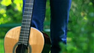 Teenage girl smiling and standing with her guitar in the park, steadycam shot