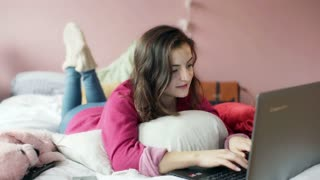 Teenage girl typing on laptop and smiling to the camera