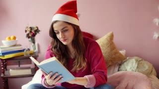 Teenage girl wearing Santas hat and reading book in her bedroom