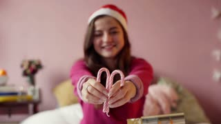 Teenager wearing Santas hat and showing candy cane to the camera