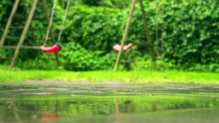 Teeter waving in playground, bad weather, slow motion shot