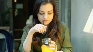 Thoughtful girl drinking beverage in the cafe and smiling to the camera