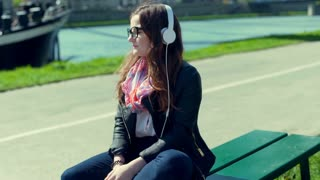 Thoughtful girl sitting on the bench and listening music on headphones