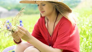 Thoughtful girl sitting on the meadow and holding field flowers, steadycam shot