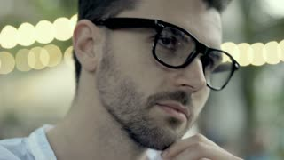 Thoutful, handsome man taking glasses and talks with someone, steadycam shot