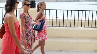 Three female friends after shopping walking on the street, steadycam shot