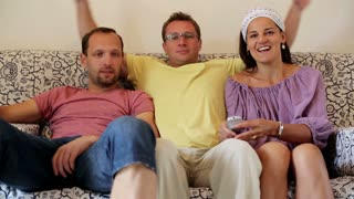 Three friends spending time watching television at home
