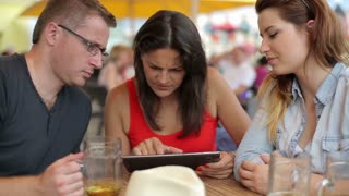 Three friends with tablet computer sitting in the restaurant, steadycam shot
