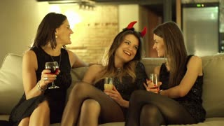 three young woman sitting on the sofa and having fun at the bachelorette party