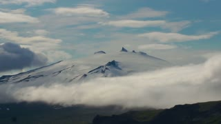 Time lapse of clouds mass rolling over snaefellsjokull snow-covered mountains in