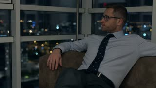 Tired businessman sitting on the sofa at night and resting