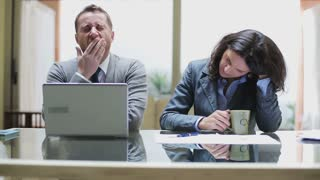 Tired businesspeople finish working in the office and drinking coffee