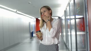 Tired businesswoman yawning while drinking coffee on hallway