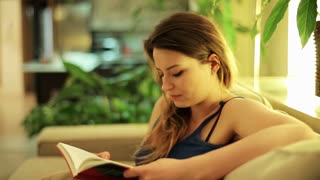 Tired woman finish reading book on sofa at night.