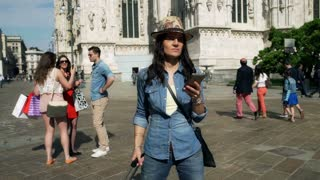 Tourist walking with luggage and using smartphone, steadycam shot