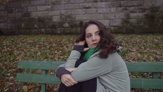 Troubled woman sitting on the bench, steadycam shot, slow motion shot at 240fps