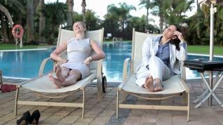 Two businesswomen relaxing on sunbed by poolside