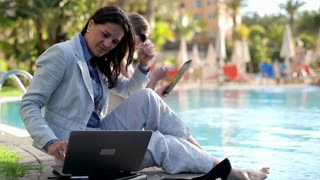Two businesswomen sitting by the poolside and working using technology