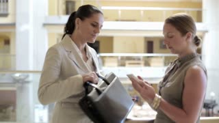 Two businesswomen with cellphone in office corridor, steadycam