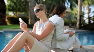 Two businesswomen with cellphones relaxing on sunbed by the poolside