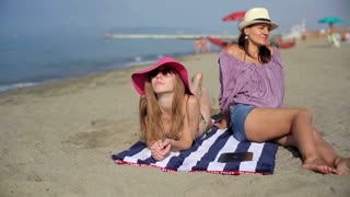 Two female friends relaxing on the beach