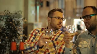 Two guys drinking beer and talking in the restaurant at night, steadycam shot