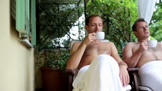 Two guys with cups of tea talking and relaxing in spa resort, outdoors