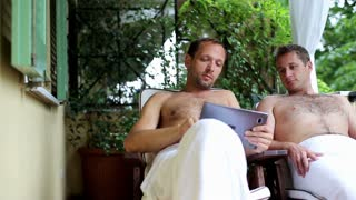 Two guys with tablet computer relaxing in spa resort, outdoors