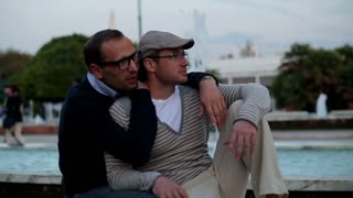 Two handsome men sitting on bench and smiling to the camera, slow motion