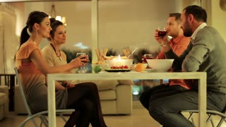 Two happy couples drinking wine and talking.