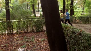 Two women jogging on the pathway in the park, steadycam shot