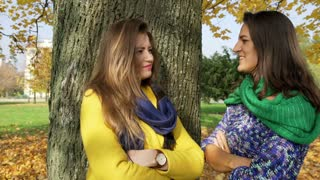 Two women standing next to the tree in the park and chatting