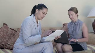 Two young businesswomen sitting in hotel lounge with laptop and documents