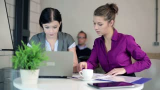 Two young businesswomen with laptop and documents in the office