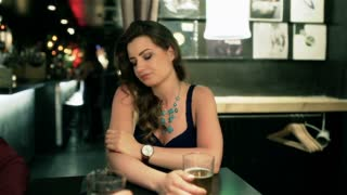 Uhappy woman sitting alone in the pub, steadycam shot