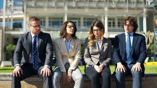 Unhappy businesspeople showing thumbs down to the camera while sitting outdoors,