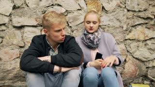 Unhappy girl shouting on her boyfriend while sitting