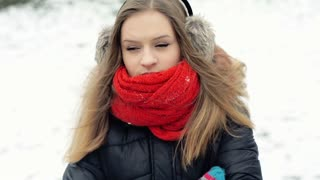Unhappy girl standing in the snowy park and thinks about something, steadycam