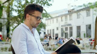 Unhappy man finish reading a book and looking disappointed