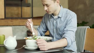 Unhappy man thinks abouts something while eating healthy lunch, steadycam shot