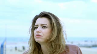 Unhappy woman sitting at the sea, steadycam shot, slow motion shot