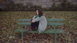 Unhappy woman sitting on the bench, steadycam shot, slow motion shot at 240fps