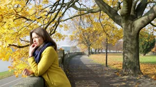 Unhappy woman standing in the autumnal park